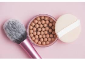 古铜色珍珠粉色背景上的海绵和化妆刷_3114919