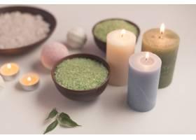 绿色草药浴盐白色背景上有照亮的蜡烛_2690874