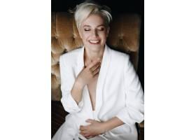美丽微笑的金发时装模特穿着白色西装坐在柔_2446773