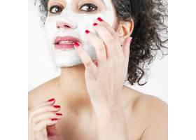 美丽的年轻女子使用白色面膜的特写_3196230