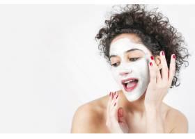 美丽的年轻女子将面膜涂在脸上与白色背景_3186739
