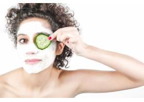 美丽的年轻女子戴着口罩用黄瓜片遮住眼睛_3196318