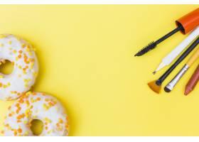 黄色背景上白色甜甜圈和化妆刷口红睫毛_3019465