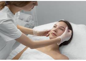 美容师和女客户在沙龙进行面部护理例行公事_12780837
