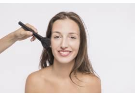 美容师在微笑的女人身上涂粉_3039309
