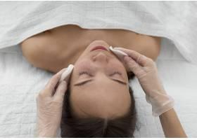 美容院的女客户使用洁面盘进行日常面部护理_12780839