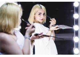 年轻女孩在镜子前化妆摆姿势_1191110