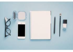 桌上有笔记本和化妆品的智能手机_3858490