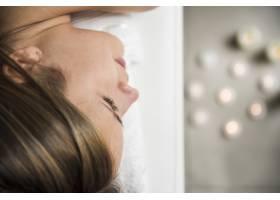 水疗中心里一名放松的年轻女子脸部的特写镜_3442672