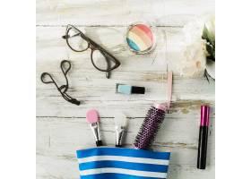 化妆袋附近的眼镜和化妆品_2062627