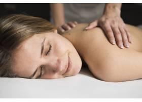 治疗师手在水疗中心为美丽的年轻女子按摩的_3453442