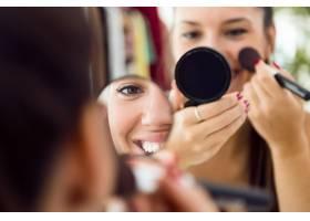 漂亮的年轻女子在家里镜子旁化妆_1624243