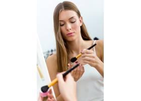 漂亮的年轻女子在家里镜子旁化妆_1624859
