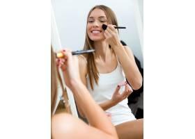 漂亮的年轻女子在家里镜子旁化妆_1624864