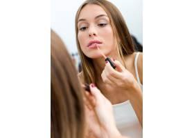 漂亮的年轻女子在家里镜子旁化妆_1624865