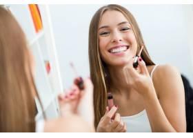 漂亮的年轻女子在家里镜子旁化妆_1624870