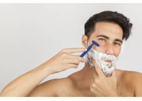男子用剃须刀刮胡子_1172338