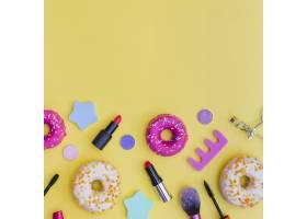 甜甜圈特写口红睫毛夹黄色背景上的化_3019461