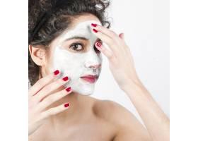 一名妇女在白色背景下在脸上涂抹面膜_3196244