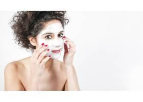 一名年轻女子在白色背景上涂抹面膜_3196250