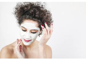 一名年轻女子在白色背景下在脸上涂抹化妆品_3196215