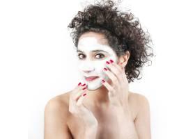 一名留着卷发的女子在白色背景下在脸上涂抹_3196259