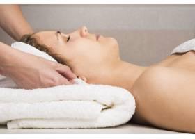 一名美容师用手包裹毛巾贴在妇女头上的特写_3442507