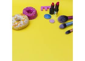 两个涂有口红的甜甜圈眼影和三把黄底化妆_3006333