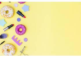 俯瞰甜甜圈口红睫毛夹黄色背景上的化_3019459