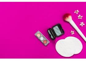 眼影调色板化妆刷粉色背景上的棉垫和花_4435648