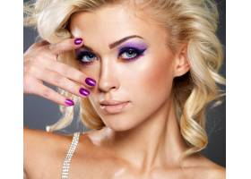 美丽的金发女子修剪紫色的指甲化着眼妆_11555492