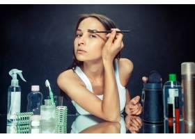 美女化妆美丽的女孩照镜子用刷子涂抹化_12495056