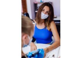 美甲美容院里戴着防护医用口罩的年轻美女_11476290