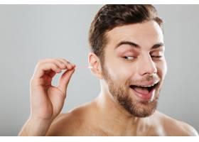 一个快活的男人清理耳朵的特写_6730404