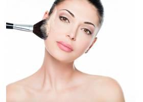 一位妇女用化妆刷在脸上涂抹干性化妆品色调_11228587