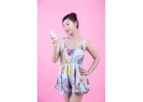 一位美丽的亚洲女子在粉色背景上拿着一瓶产_4524255