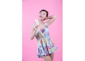 一位美丽的亚洲女子在粉色背景上拿着一瓶产_4524266