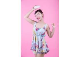 一位美丽的亚洲女子在粉色背景上拿着一瓶产_4524268