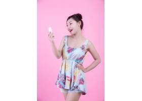 一位美丽的亚洲女子在粉色背景上拿着一瓶产_4524276