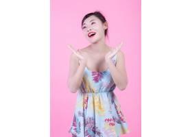 一位美丽的亚洲女子在粉色背景上拿着一瓶产_4524277