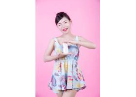 一位美丽的亚洲女子在粉色背景上拿着一瓶产_4524279