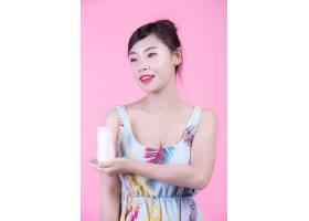 一位美丽的亚洲女子在粉色背景上拿着一瓶产_4524282