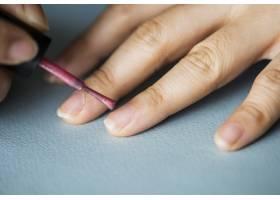 一名妇女在指甲上涂指甲油_2768409
