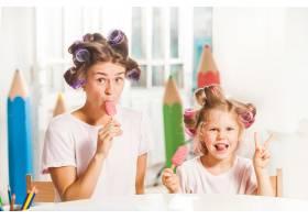 小女孩和妈妈坐在一起吃冰激凌_11315560