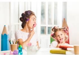 小女孩和妈妈坐在一起吃冰激凌_11648877
