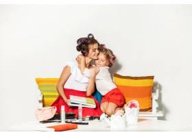 小女孩和妈妈坐在一起看着相册_9368841