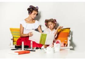 小女孩和妈妈坐在一起看着相册_9971943