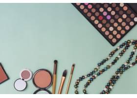 眼影调色板珠子项链粉色背景上带化妆刷_3038111