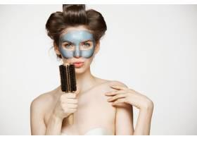 年轻滑稽女子的肖像戴着卷发和面膜在梳_9028464