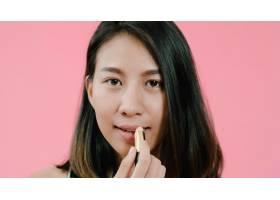 年轻漂亮时尚的亚洲女子在粉色背景上用_4395058